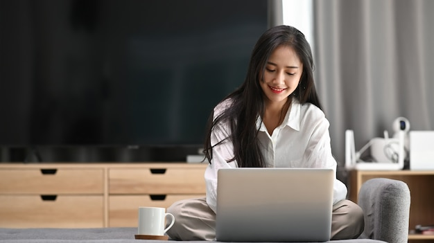 Female freelancer in her casual home clothing working on laptop and sitting on sofa in living room.
