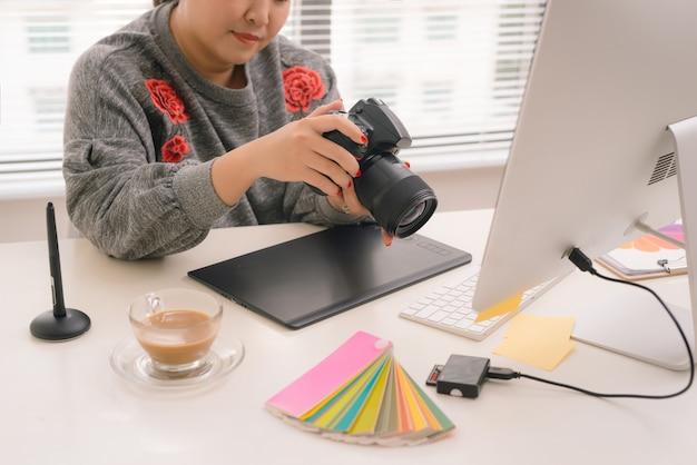 여성 프리랜서 사진가는 워크스테이션의 테이블에 앉아 디지털 카메라로 사진을 확인합니다.