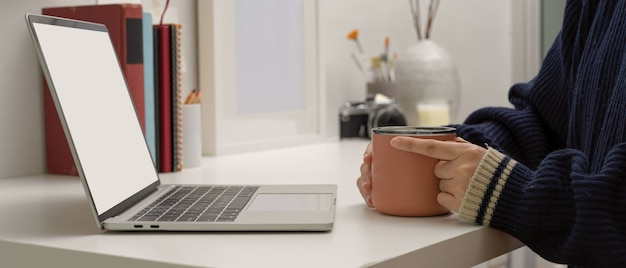 Female freelancer sitting at home office and holding coffee mug while looking on mock up laptop