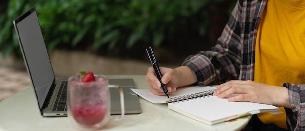 庭でノートパソコンのモックアップで作業しながらノートにメモを取る女性のフリーランサー
