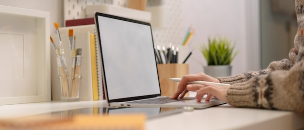 Female freelancer typing on mock-up laptop on modern workspace with painting tools and supplies