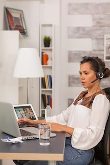 Женский фрилансер в наушниках во время видеозвонка, работая из домашнего офиса.