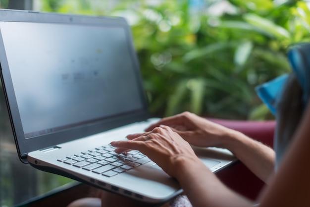 プロジェクトに取り組んでいる女性フリーランサー、カフェテラスに座っている彼女のラップトップでインターネットで情報を入力、検索しています。