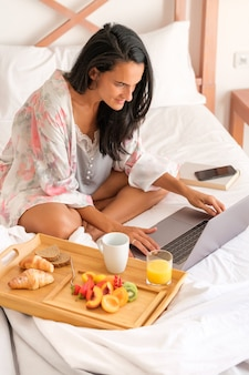 Female freelancer working online in bedroom