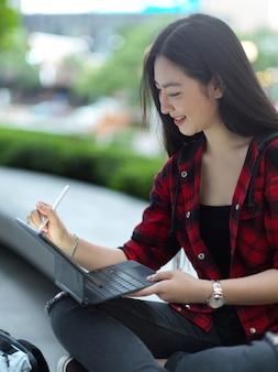 공원에서 휴식을 취하는 도시 공원 대학생에서 스타일러스 펜으로 태블릿을 작업하는 여성 프리랜서
