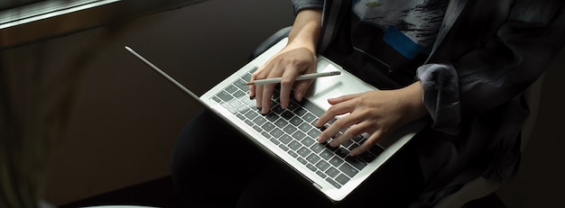 Female freelancer working with laptop on her lap while sitting on the chair next to window
