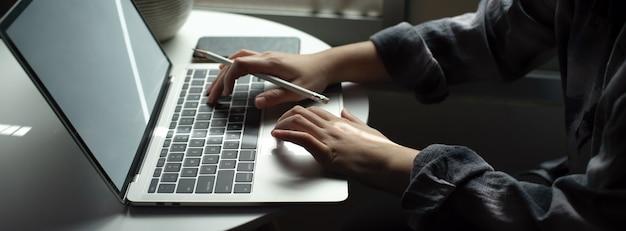Женский фрилансер работает с ноутбуком на круглом столе рядом с окном в гостиной