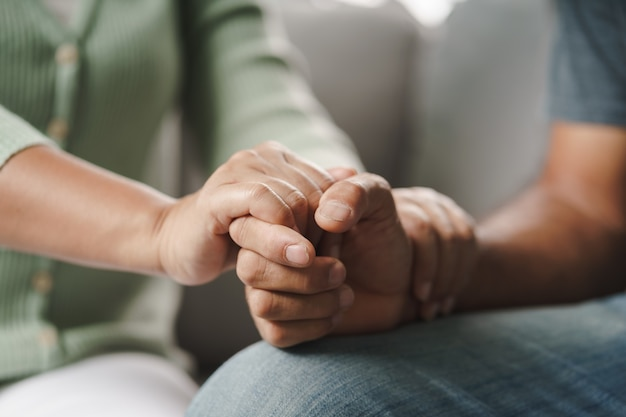 Female friend or family sitting and hold hands during cheer up to mental depress man, psychologist provides mental aid to patient. ptsd mental health concept