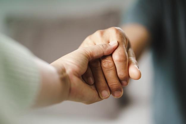 여성 친구나 가족이 정신적으로 우울한 남성을 위로하는 동안 손을 잡고 있는 심리학자는 환자에게 정신적 도움을 제공합니다. ptsd 정신 건강 개념