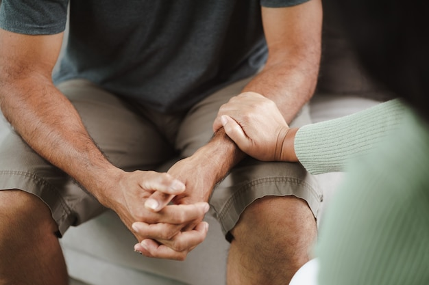 여성 친구나 가족이 앉아 정신적 우울증을 앓고 있는 남성에게 손을 잡고 심리학자는 환자에게 정신적 도움을 제공합니다. ptsd 정신 건강 개념