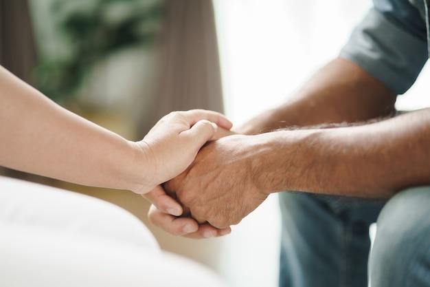 여자 친구나 가족이 앉아 정신적 우울한 남자를 격려하는 동안 손을 잡고 심리학자는 환자에게 정신적 도움을 제공합니다. ptsd 정신 건강 개념
