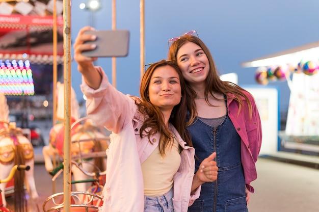 Amici femminili al parco di divertimenti che prendono selfie