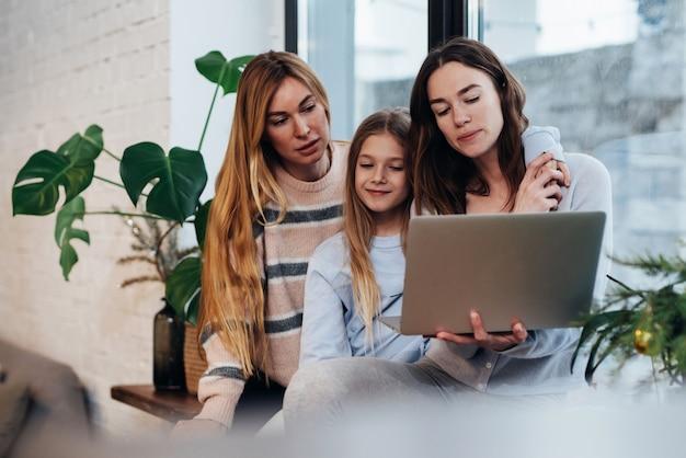 Подружки и маленькая девочка сидят дома на подоконнике и смотрят сериал.