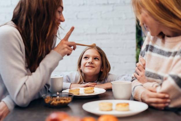 여자 친구와 어린 소녀가 함께 테이블에 앉아 식사를 하고 이야기를 나누다