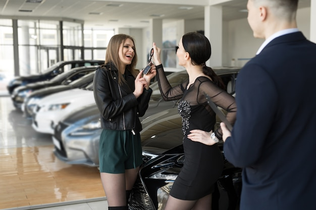 Female friends are happy to buy a car at a car dealership
