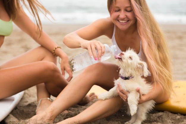 Подруги на пляже, давая собаке воду
