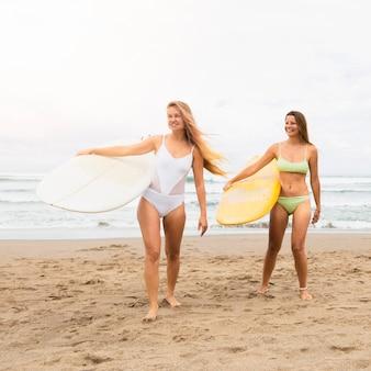 Amici di sesso femminile in spiaggia tenendo le tavole da surf
