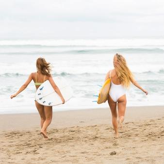 Amici femminili in spiaggia con tavole da surf