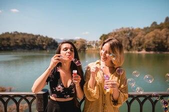 Female friends blowing bubbles near river