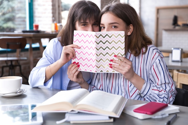 Female friends in cafe with copybook