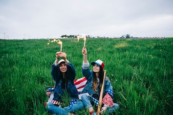 Female friends celebrating Independence Day on green grass