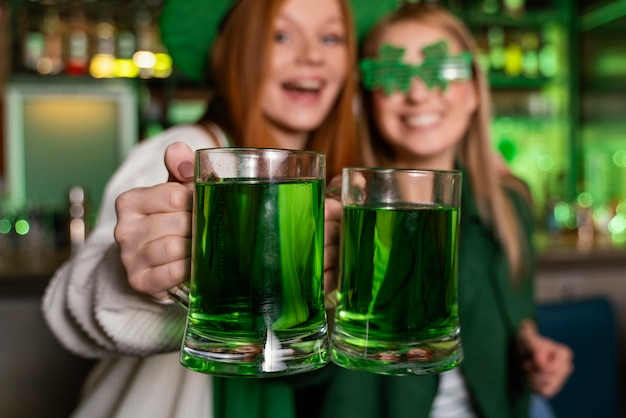 Female friends celebrating st. patrick's day with drinks at the bar
