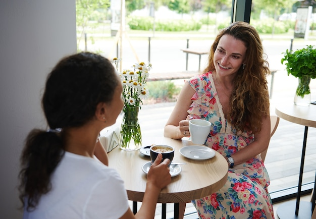 晴れた夏の日に居心地の良いカフェで一杯のコーヒーを飲みながらおしゃべりする女性の友人。女性の友情の概念