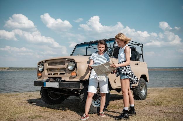 Подруги проверяют карту во время путешествия на машине