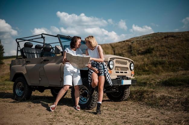 Amici di sesso femminile che controllano la mappa durante il viaggio in auto