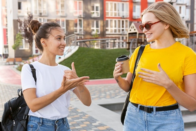 Female friends in the city using sign language