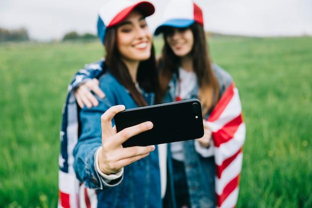 Amici femminili in berretti colorati prendendo selfie