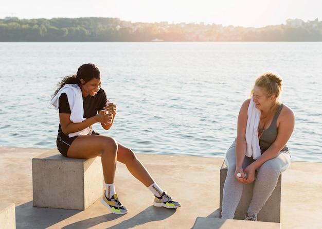 Amici di sesso femminile che conversano dopo aver lavorato in riva al lago