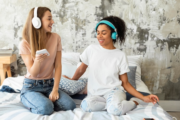 Подруги танцуют вместе на кровати у себя дома
