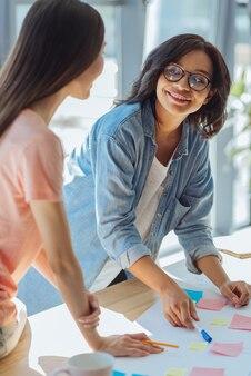 Подружки. довольная умная симпатичная женщина смотрит на подругу и улыбается, работая с ней над университетским проектом