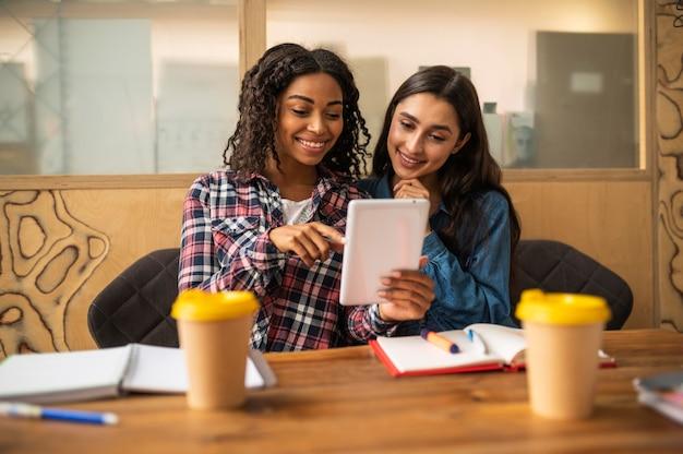 Подруги вместе делают домашнее задание с помощью планшета