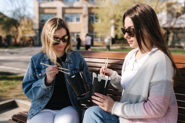 Female friends eat asian food takeaway sitting on a bench