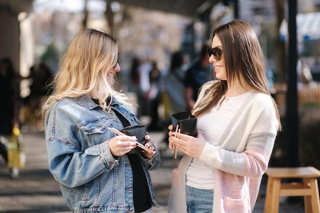 Female friends eat asian food takeaway in the street