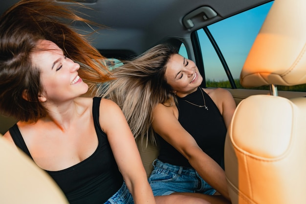 Female friends enjoy car ride, waving hair together during listen music and dance at back seat, lovely friendship