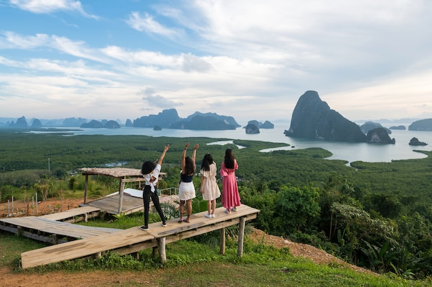 Female friends enjoy view of limestone mountain and adaman sea in phang nga bay from samed nang chee