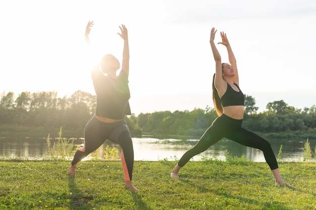 Female friends enjoying relaxing yoga outdoors in the park.