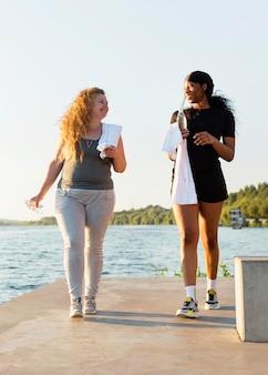 Amici femminili che si esercitano insieme in riva al lago