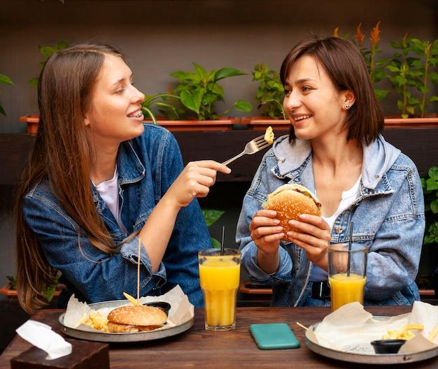 Подруги кормят друг друга гамбургерами