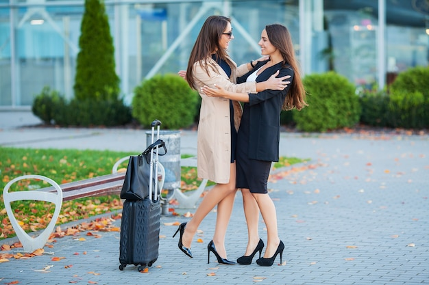 Female friends have a trip together. front view of cute brunettes with luggage at the airport
