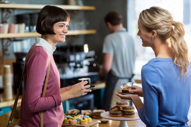 カフェで一杯のコーヒーを持つ女性の友人