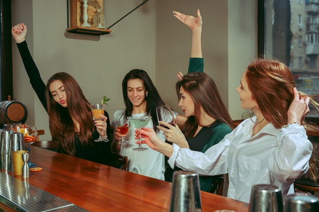 バーで飲み物を飲んでいる女性の友人。彼らはカクテルを片手に木製のテーブルに座っています。チリンと鳴るメガネです
