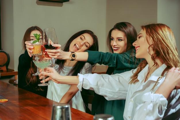 술집에서 술을 마시고있는 여자 친구. 그들은 칵테일과 함께 나무 테이블에 앉아 있습니다. 땡땡이는 안경