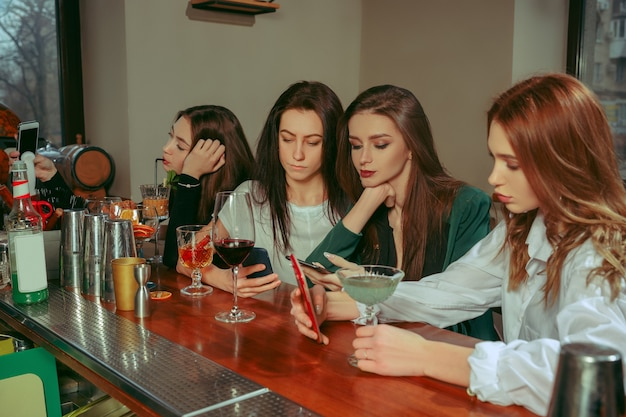 バーで飲み物を飲んでいる女性の友人。彼らはカクテルを片手に木製のテーブルに座っています。彼らはカジュアルな服を着ています。