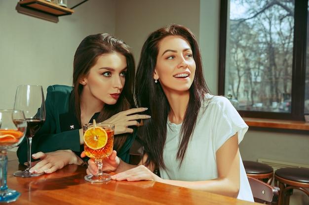 술집에서 술을 마시고있는 여자 친구. 그들은 칵테일과 함께 나무 테이블에 앉아 있습니다. 그들은 평상복을 입고 있습니다.