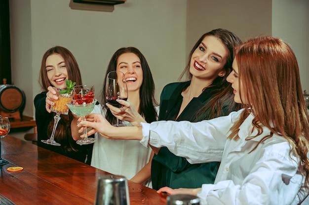 バーで飲み物を飲んでいる女性の友人。彼らはカクテルを片手に木製のテーブルに座っています。