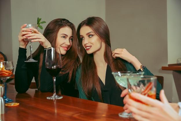 Подруги с напитками в баре. они сидят за деревянным столом с коктейлями.